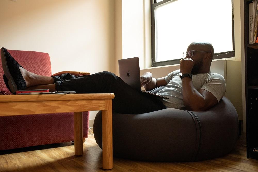 man using laptop sitting on bean bag