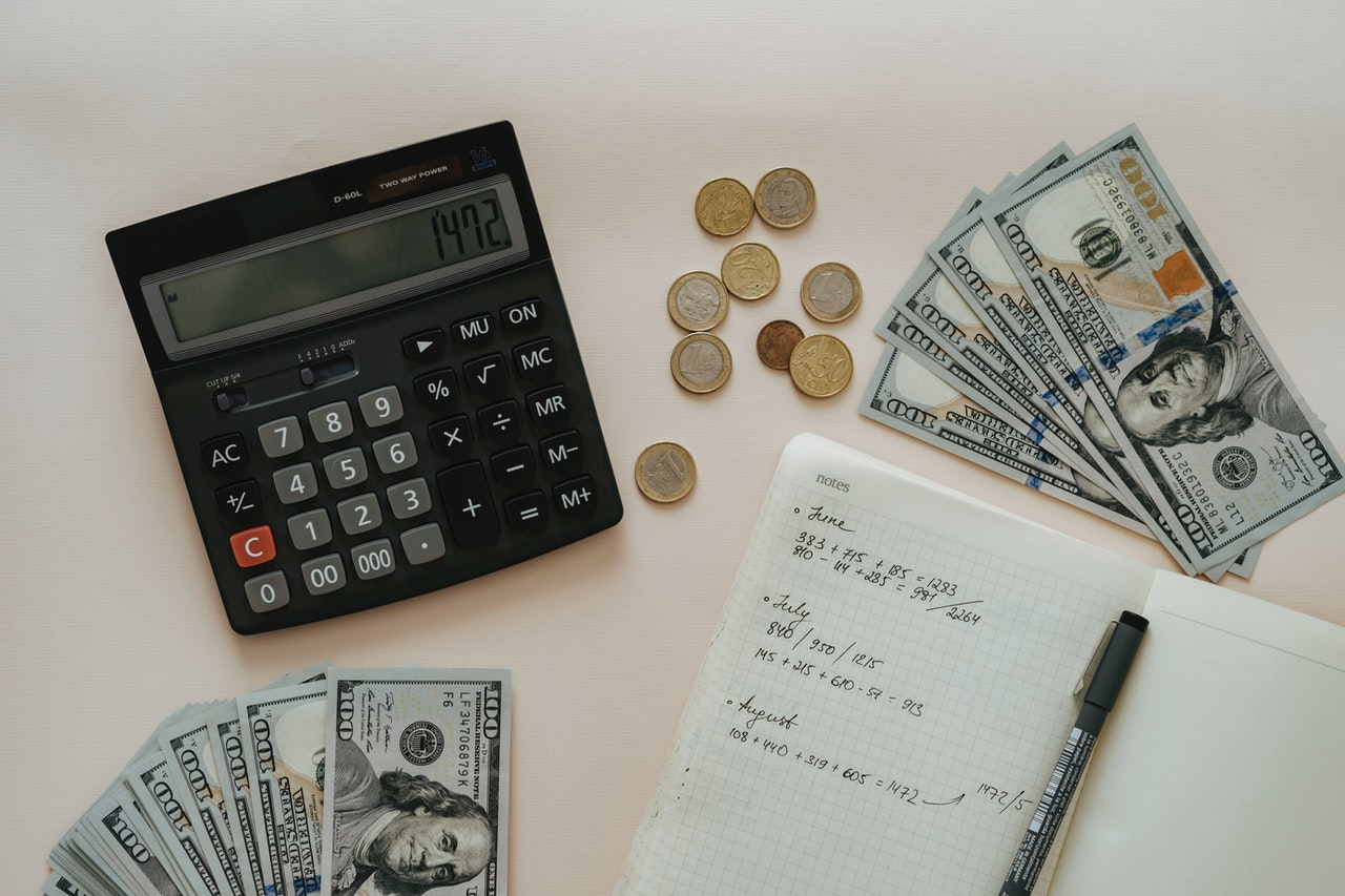 Money, calculator, notebook and pen on a white table