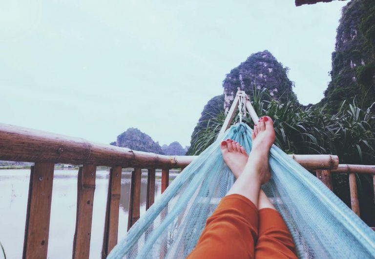 Pernas de uma mulher deitada na rede, com vista para as montanhas