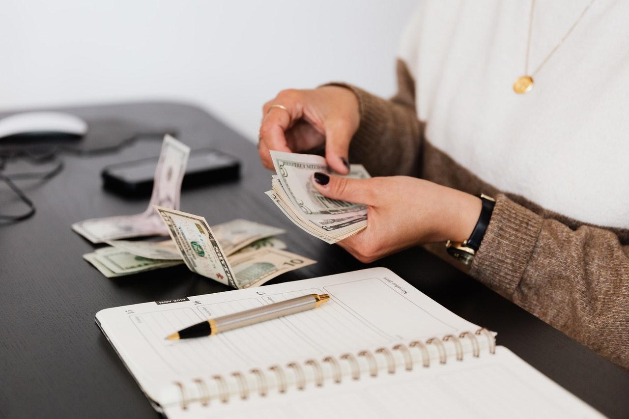 Persoon telt geld aan een bureau