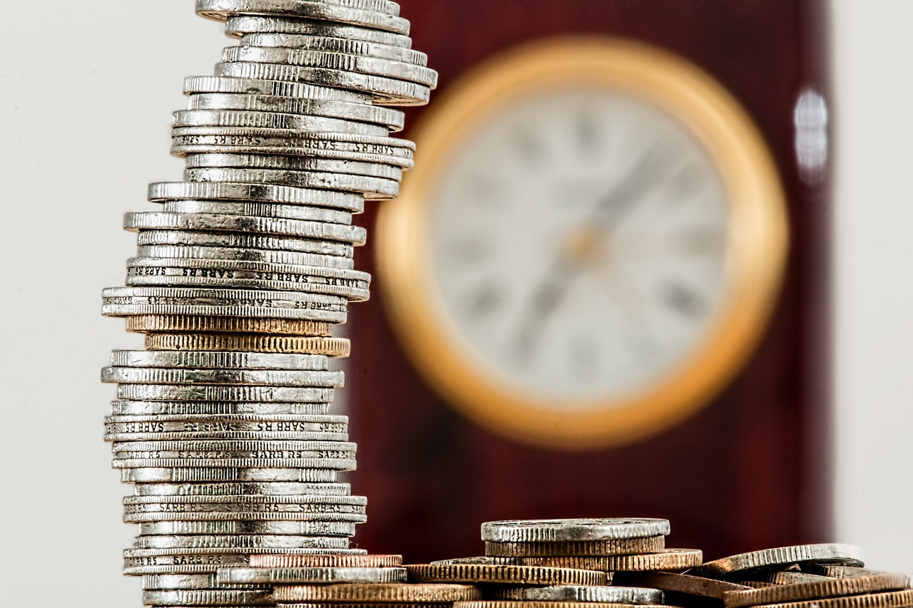A pile of coins with a clock in the background