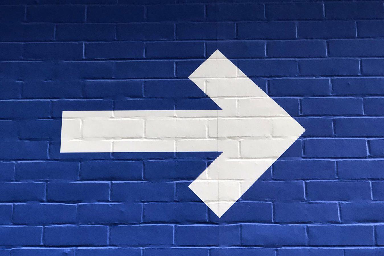 white-arrow-on-blue-background