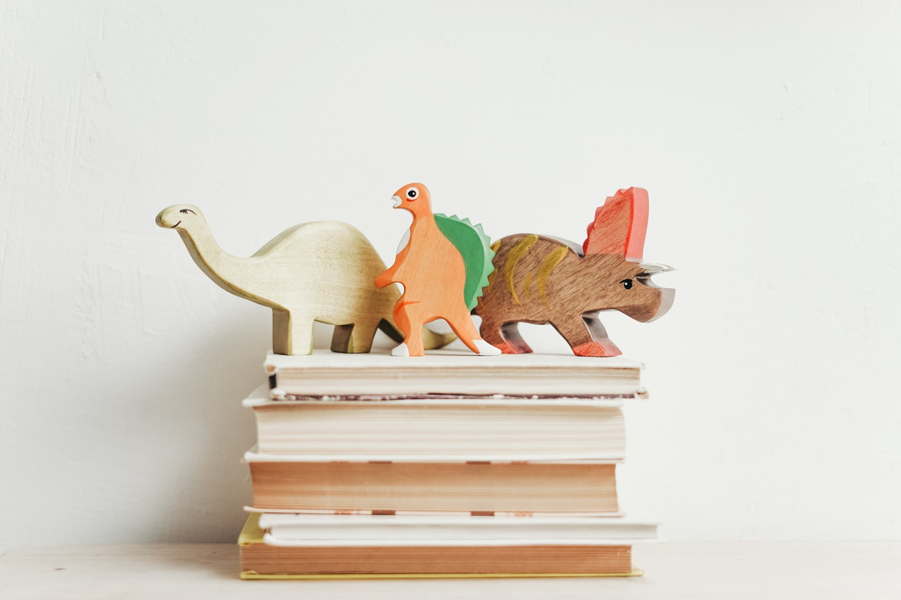 Wooden dinos on a pile of books against a white background