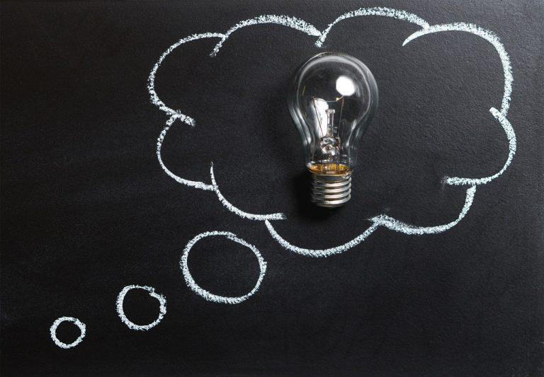 Quadro negro com o desenho de um balão de pensamento com uma lâmpada dentro