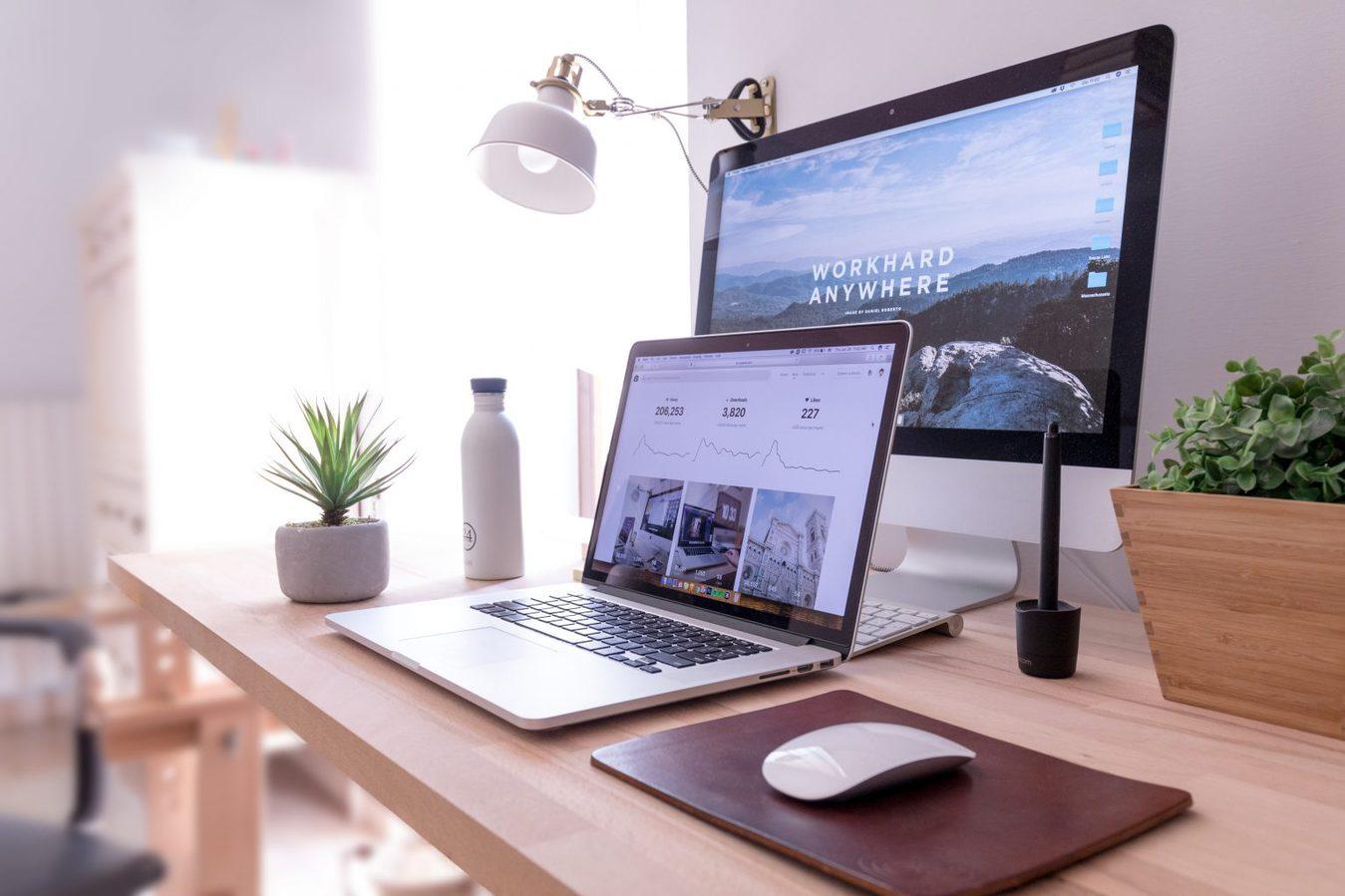 desk with desktop and laptop computers set up