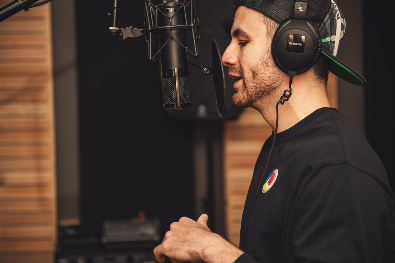 man wearing headphones speaking into studio microphone