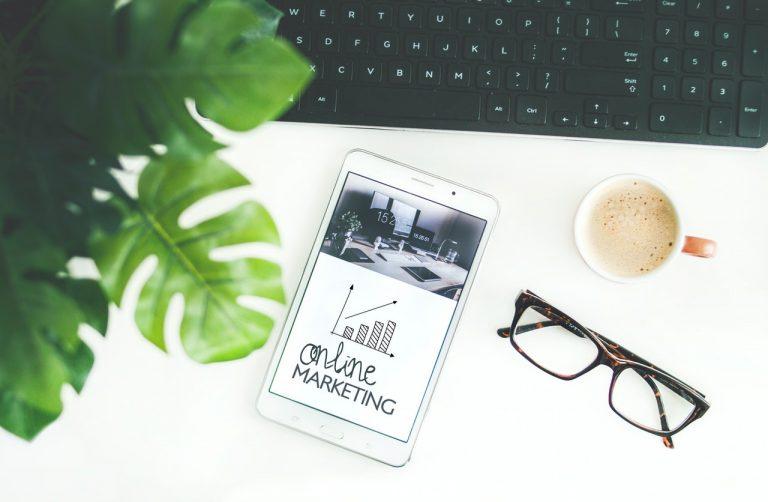 """Mesa branca com uma planta, óculos, xícara de café e um tablet com a frase """"online marketing"""" na tela"""