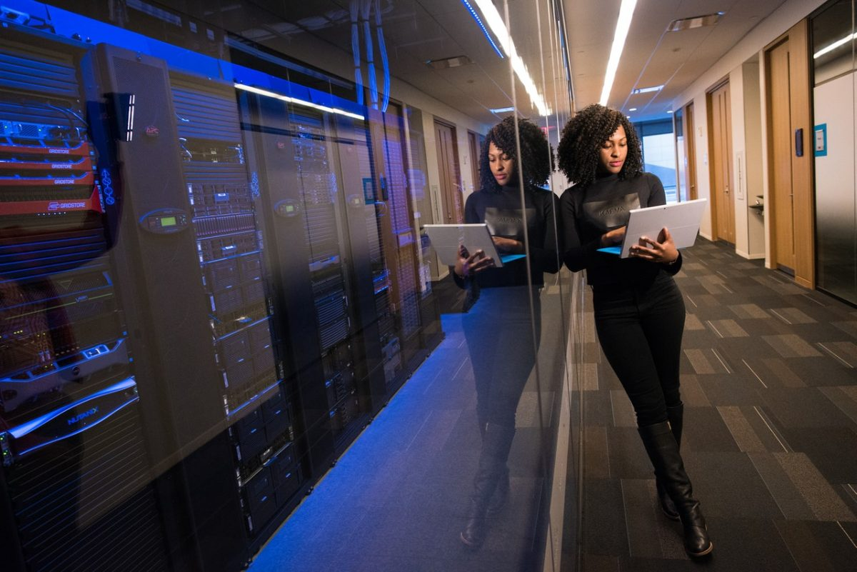 Moça com notebook na mão em um cômodo cheio de servidores