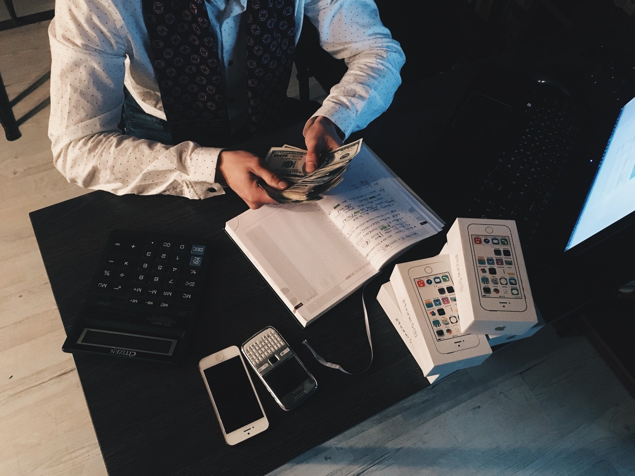 A person calculating accounts inside over a dark table
