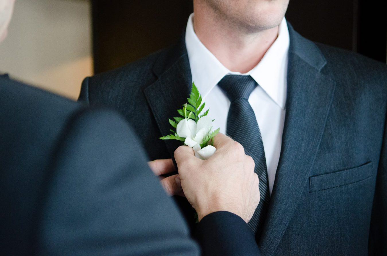person putting buttonhole flower on man's suit