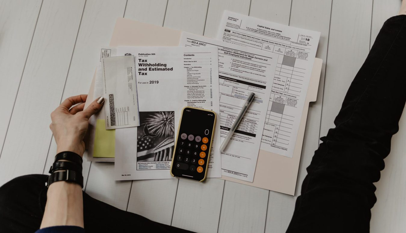 person sitting on floor with papers and calculator