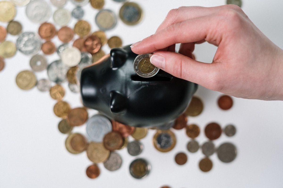 Um cofre de porquinho rodeadode moedas, visto de cima