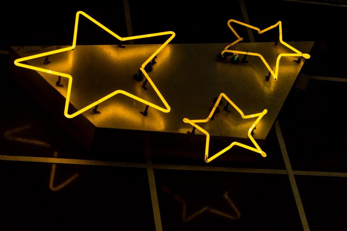 Três estrelas amarelas de neon com fundo preto