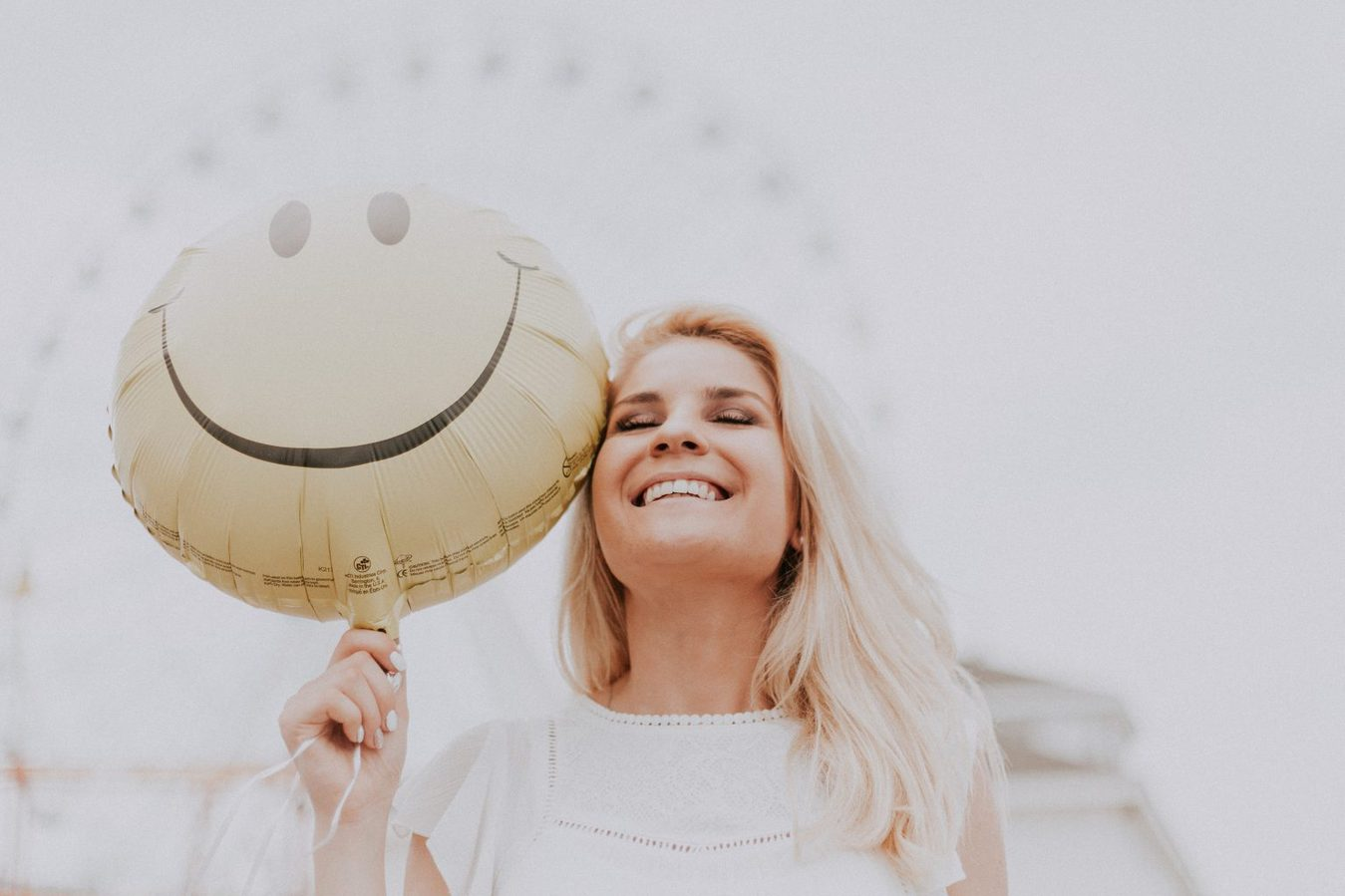 woman holding smiling emoji balloon and laughing