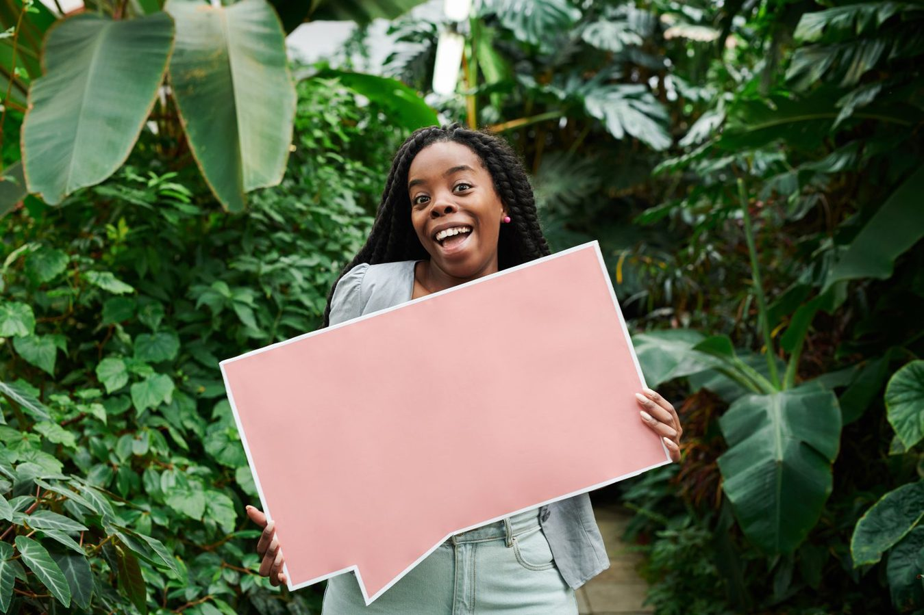 woman standing amid plants holding giant pink speech bubble