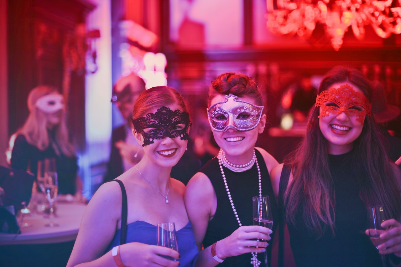 Women indoors at a party wearing masks