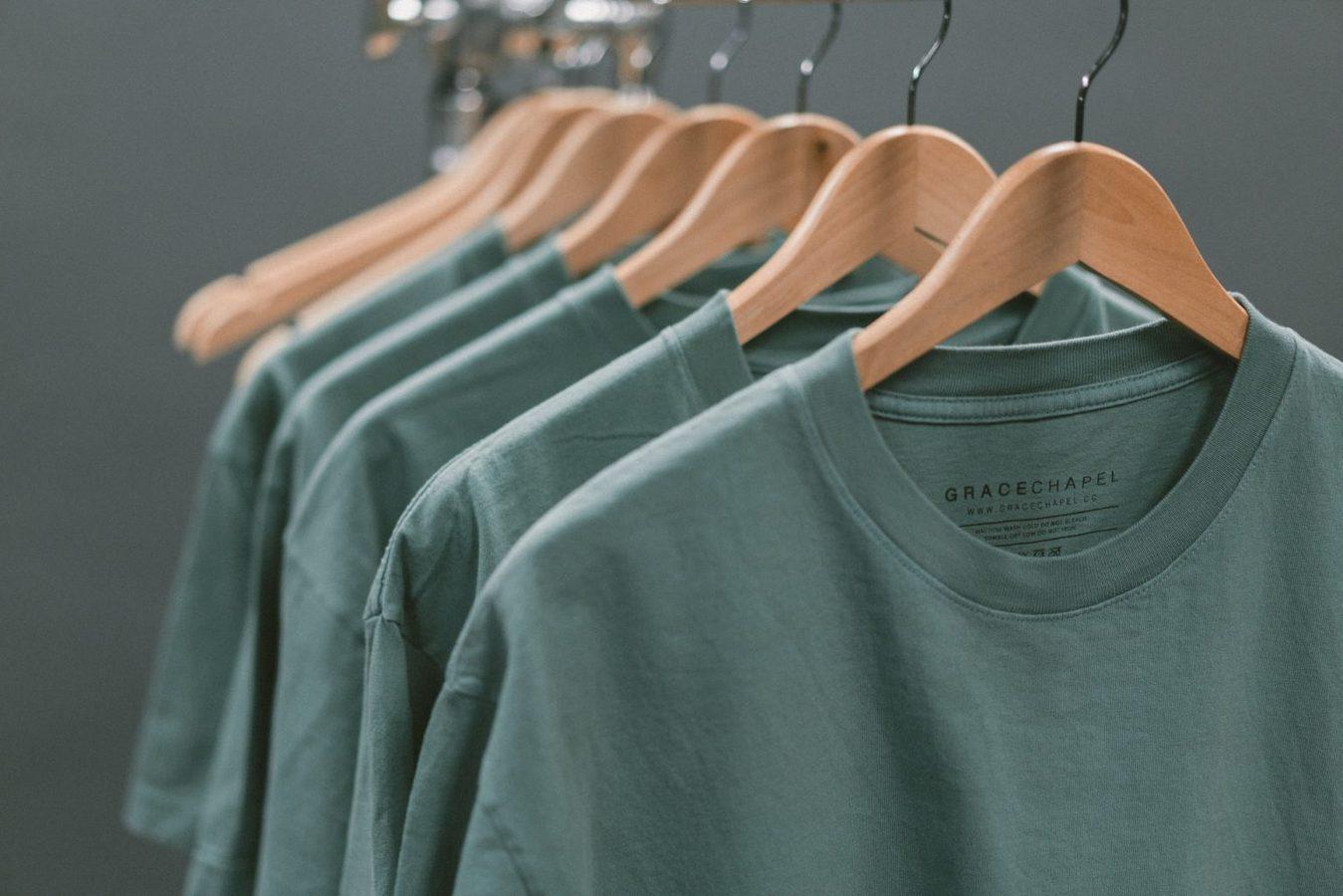 Cận cảnh áo phông màu xanh lá cây treo trên kệ