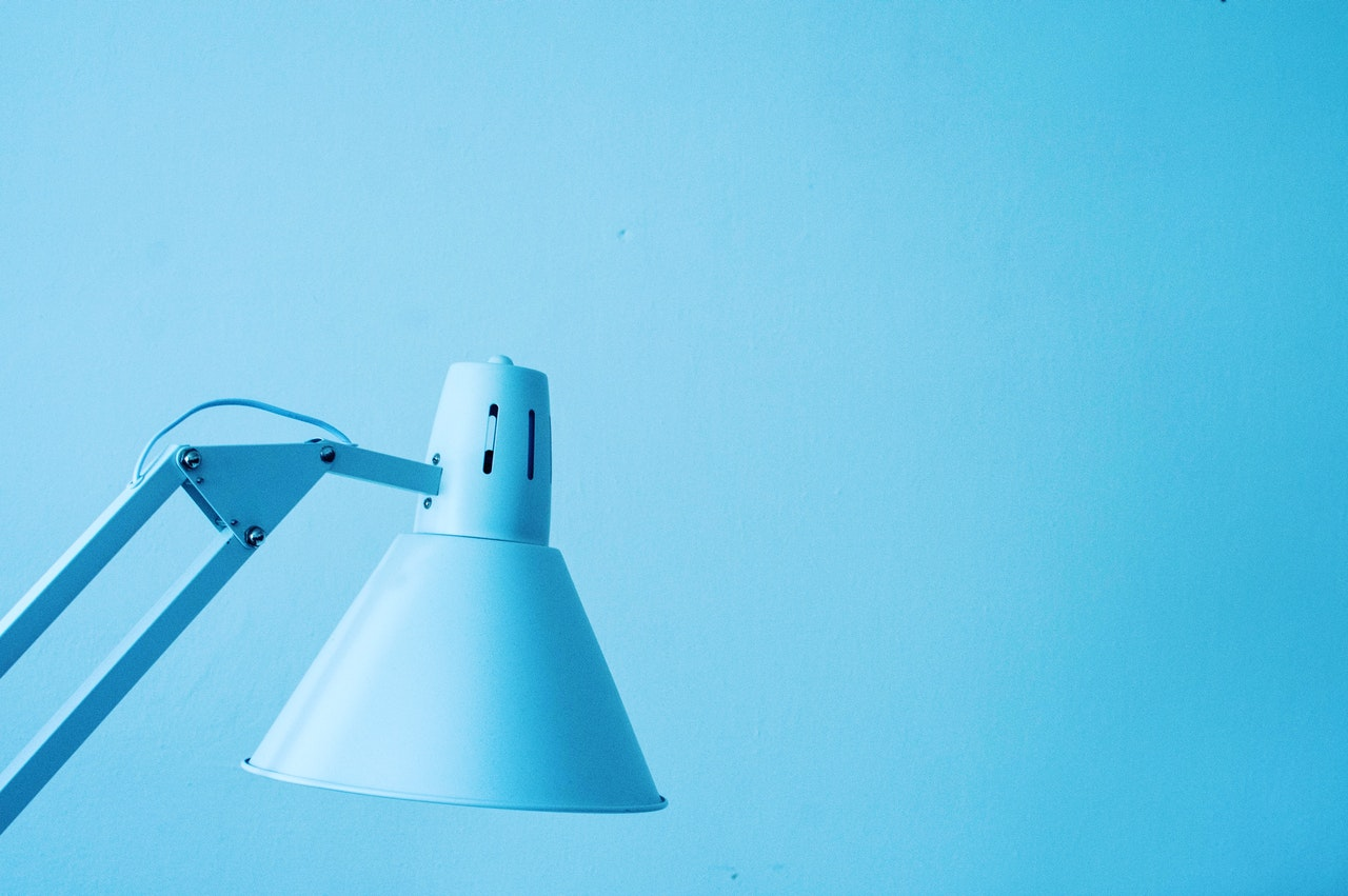 Een blauwe bureaulamp tegen een blauwe achtergrond