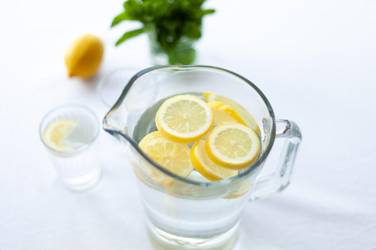 Een waterkan vol met citroen doordrenkt water tegen een witte achtergrond