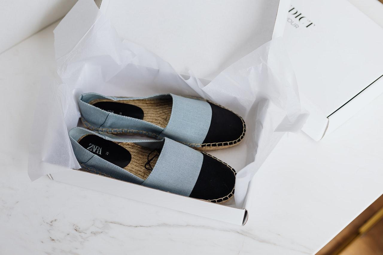 Desempacotando sapatos recebidos em uma caixa branca com papeis brancos