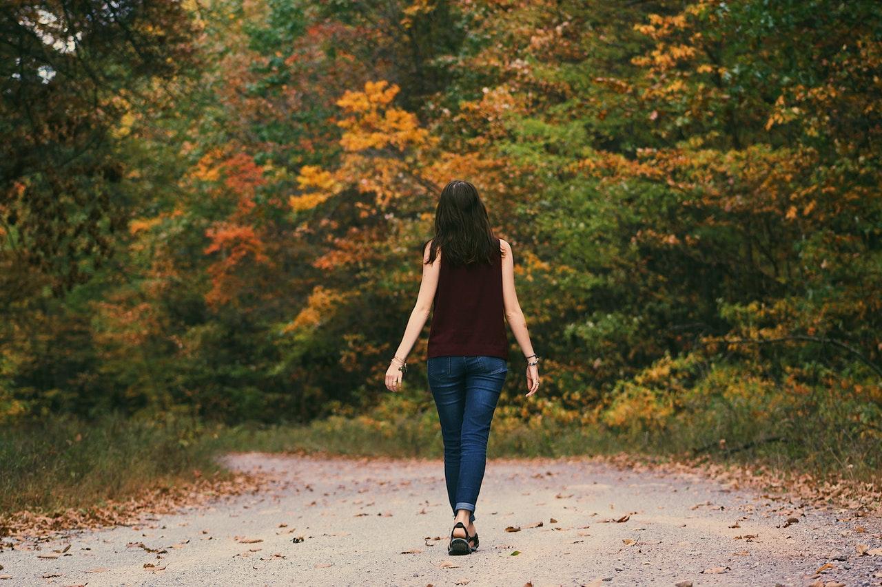 Donna che cammina in un parco in autunno