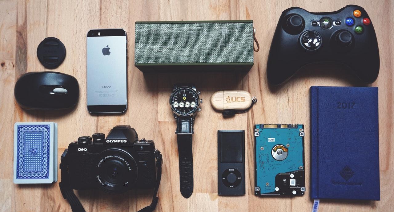 Dispositivos eletrônicos dispostos sobre uma mesa de madeira