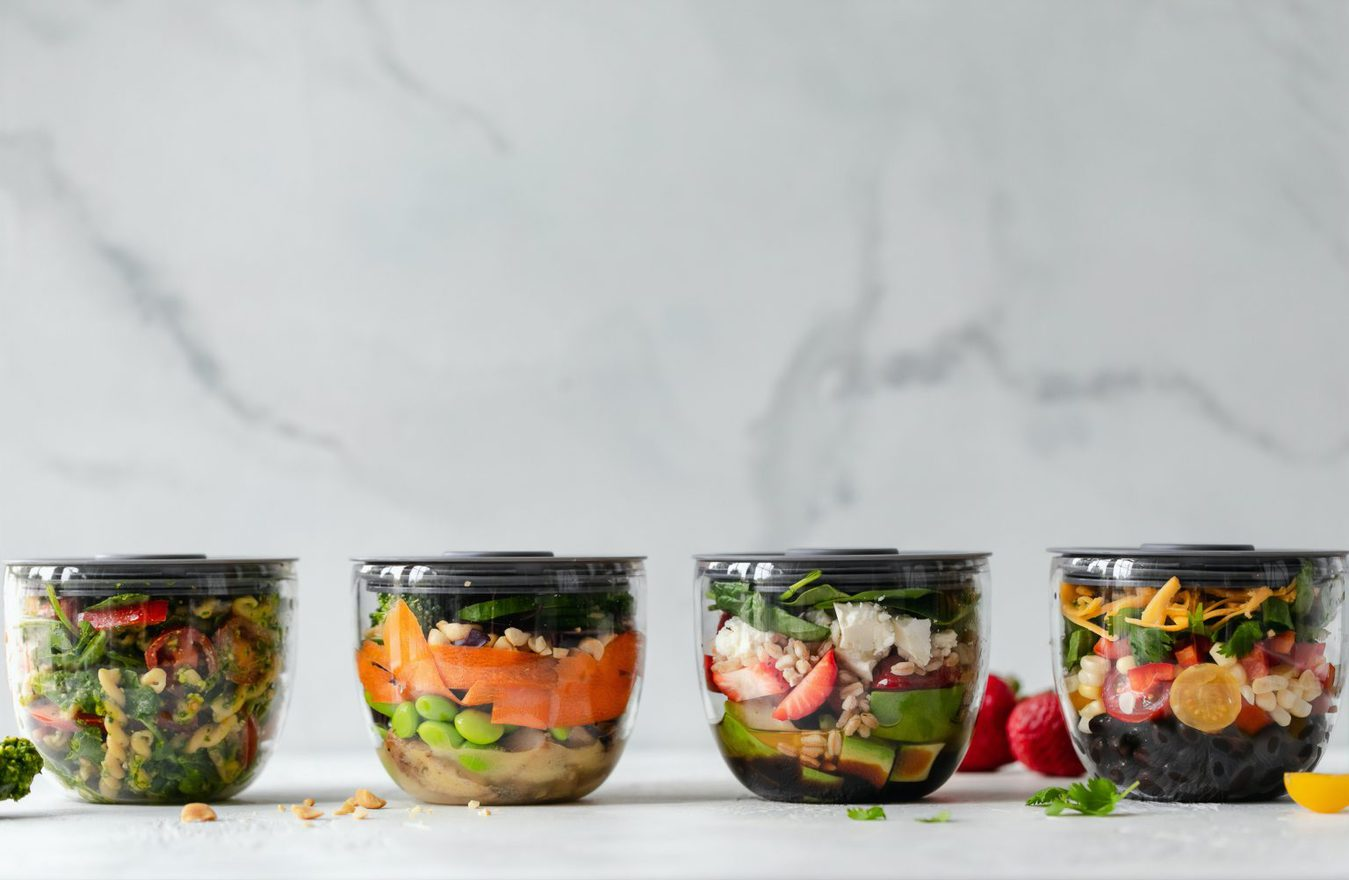 four pots of layered salad in a row