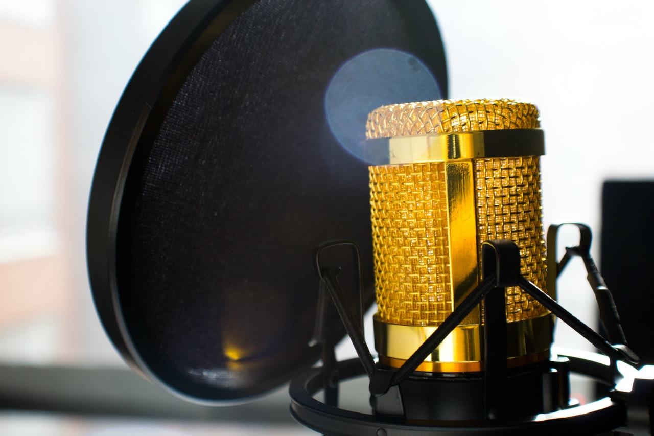 Micrófono dorado detrás de una pantalla