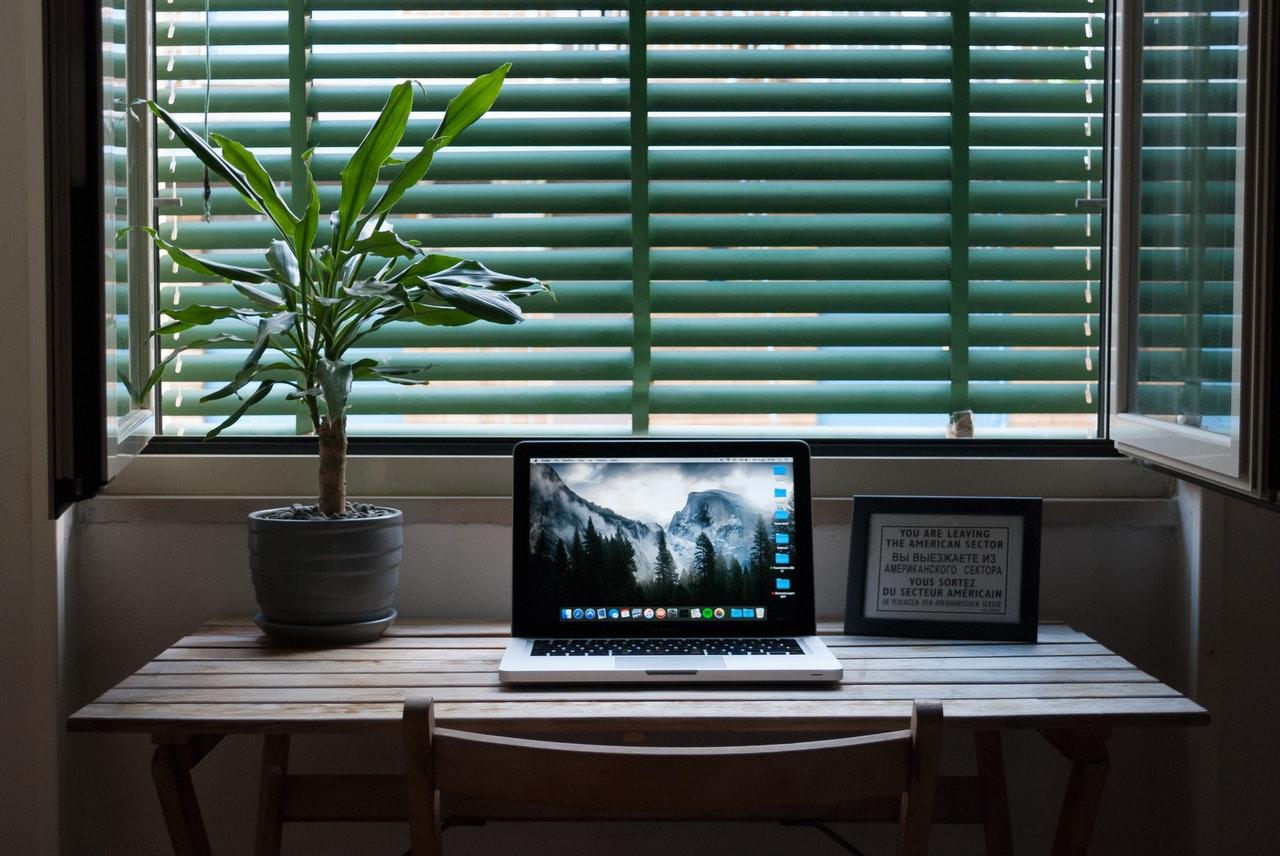 Een laptop op een bureau naast een raam en een potplant