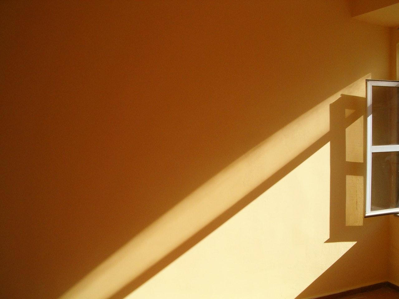Licht op een muur die uit een raam komt
