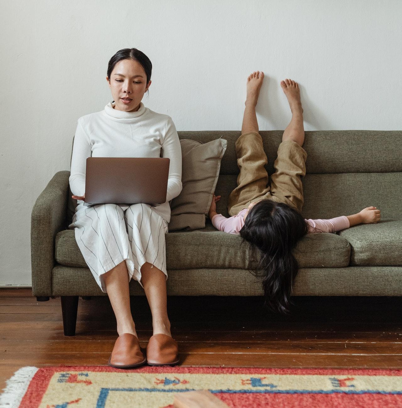 Mãe trabalhando no sofá com filha ao lado