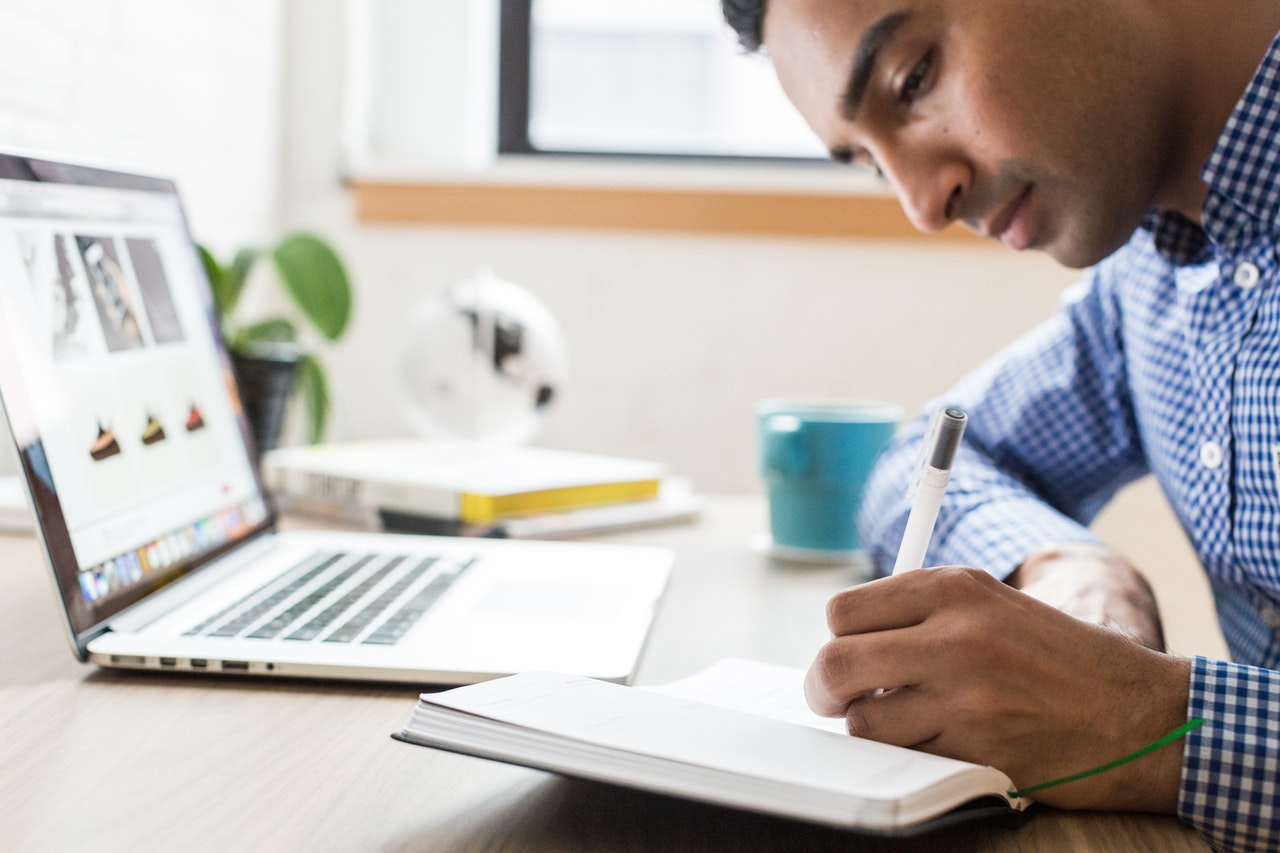 A man going over documents and taking notes in a notebook by a desk