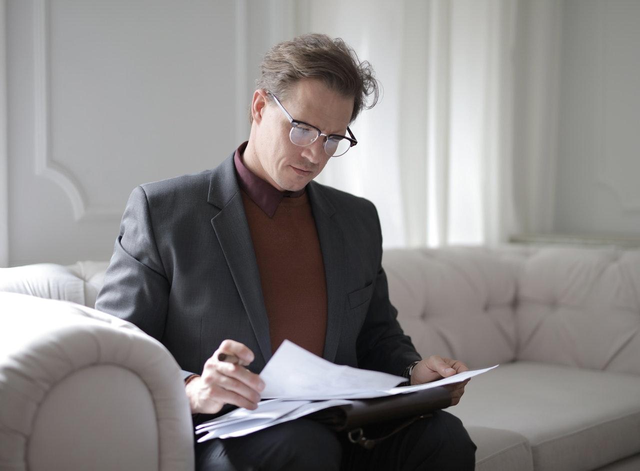 Een man in een pak die documenten leest op een witte bank