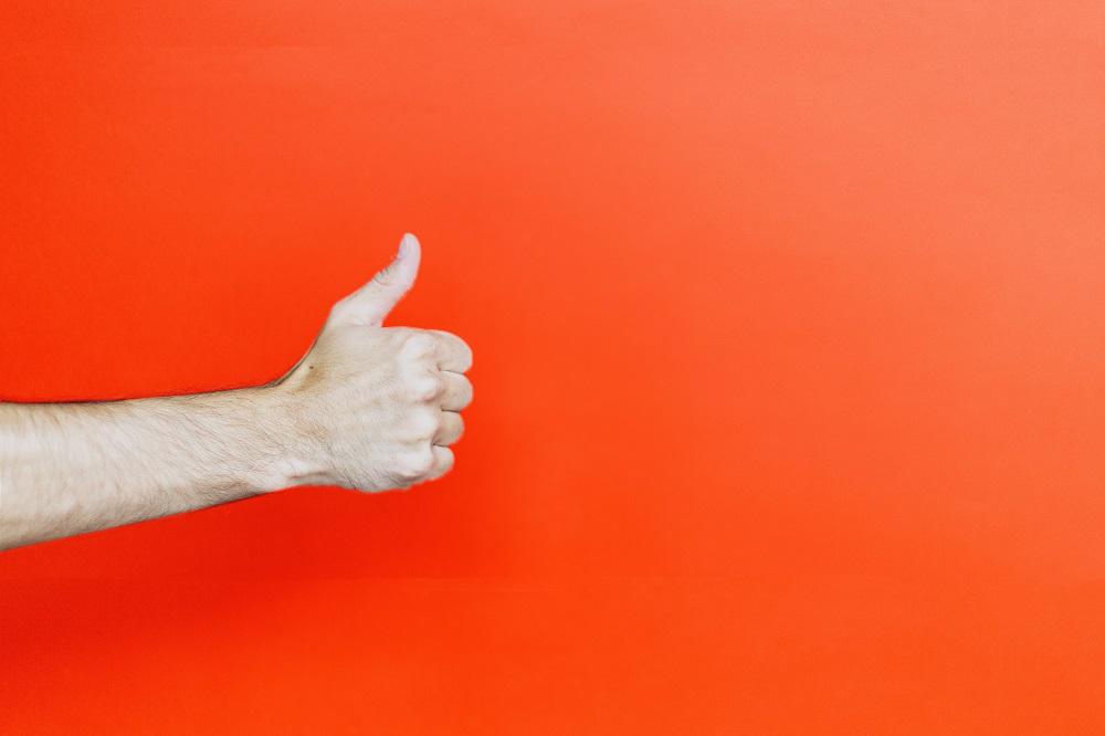 Mano di una persona che tiene un pollice in su davanti uno sfondo arancione