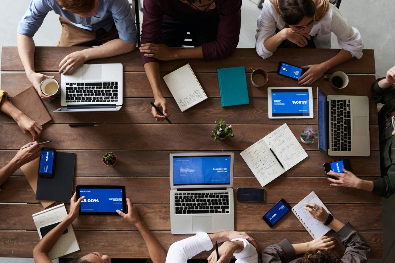 Mensen rond een houten tafel met laptops die met elkaar praten