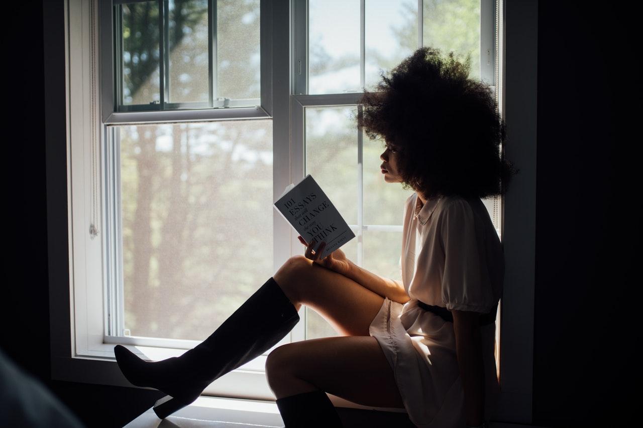 Mulher lendo um livro sentada próxima à janela