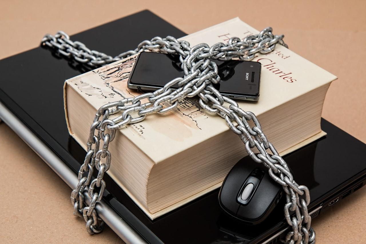 Notebook, livro, celular e mouse acorrentados e protegidos com cadeado