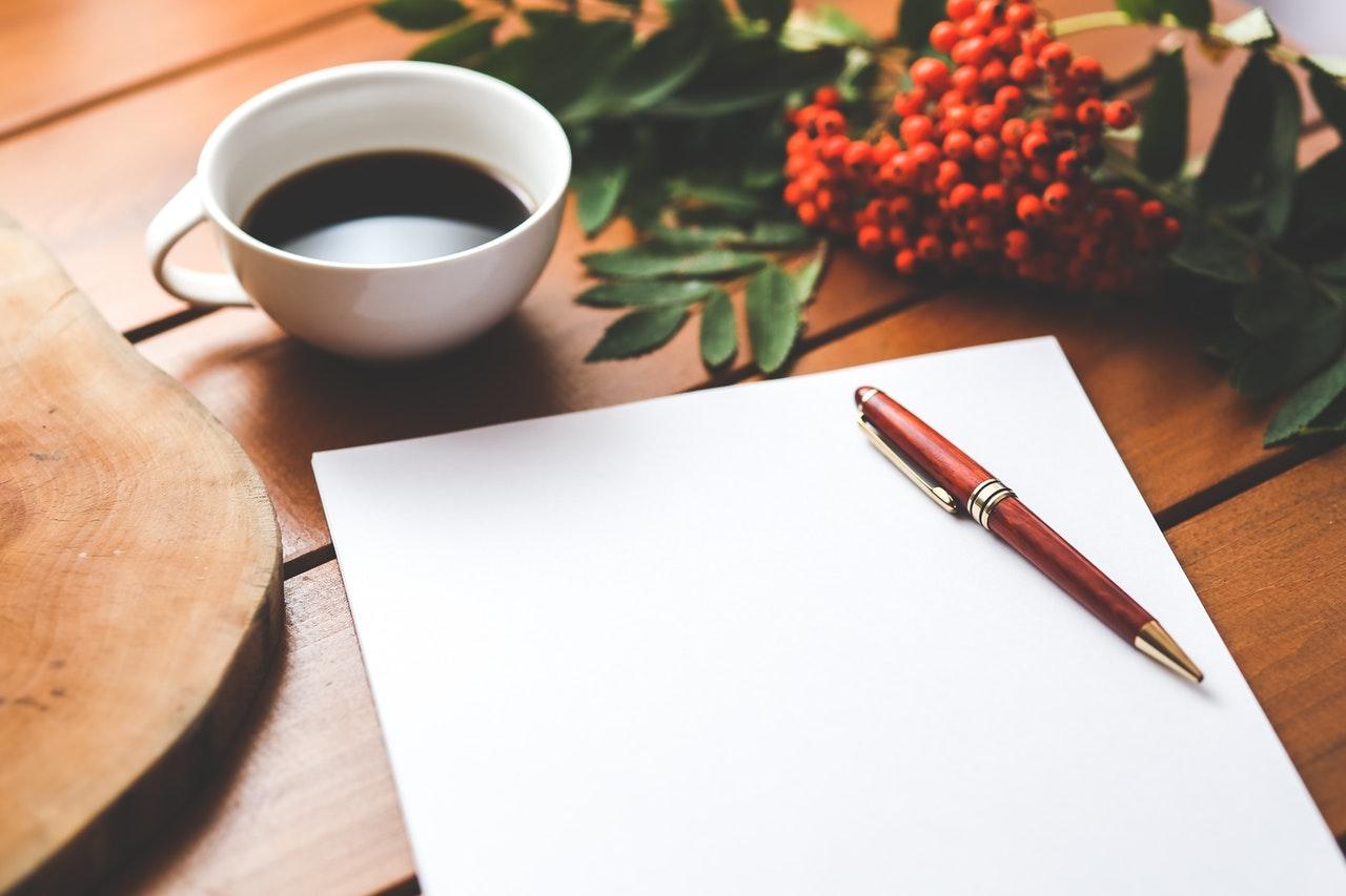 Un bloc de notas, una taza de café y un bolígrafo en un escritorio