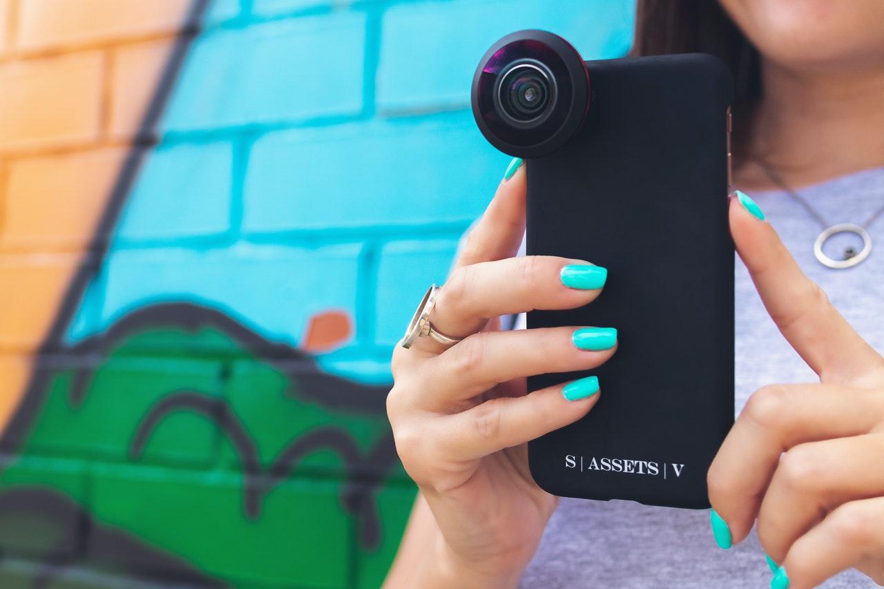 Persona che scatta una foto con un telefono dotato di obiettivo aggiuntivo