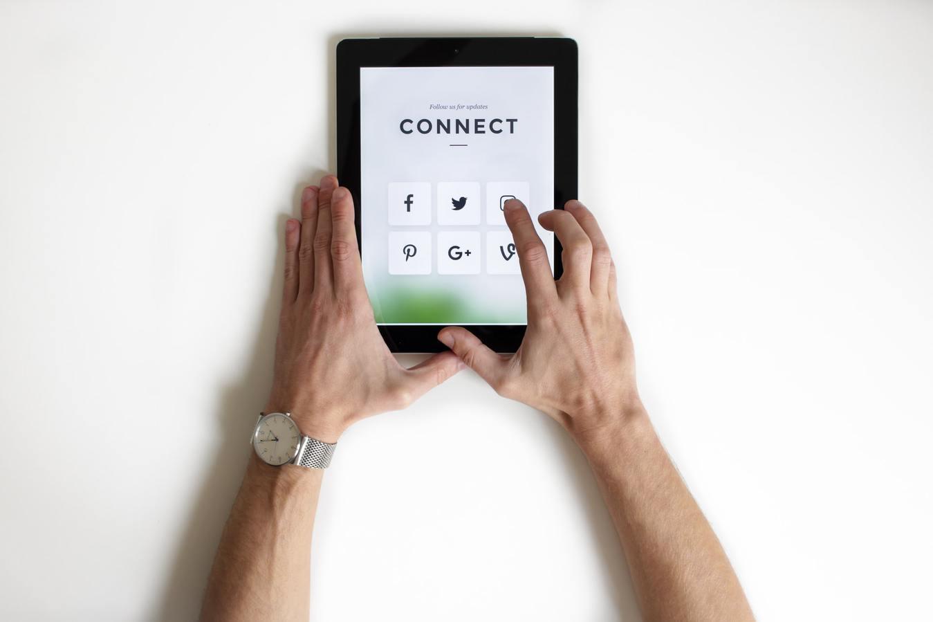 """Persona che su uno sfondo bianco tiene un tablet con la scritta """"connessione"""""""