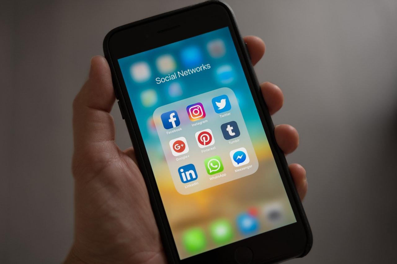 Persona che tiene un cellulare con una cartella di app di social media aperta