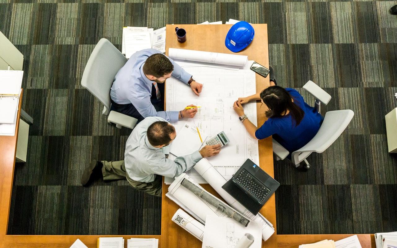 Persone sedute intorno a una scrivania con molti fogli