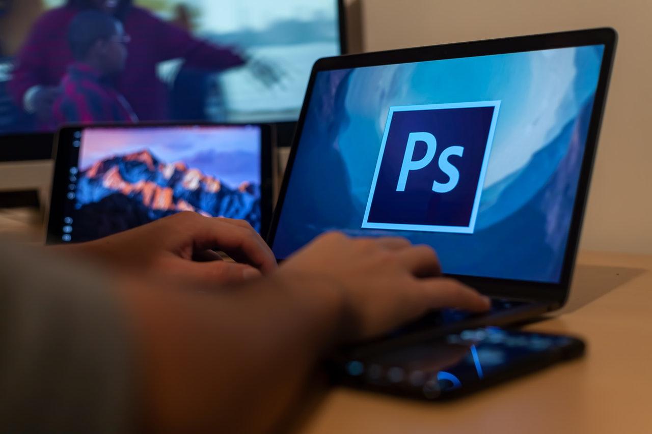 Een persoon die Photoshop op een laptop laadt om foto's te bewerken