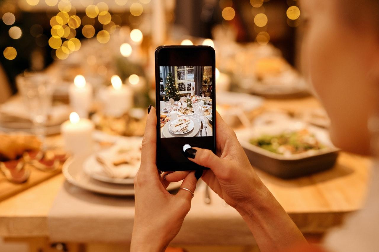 Een persoon die een foto neemt van een tafel met een telefoon