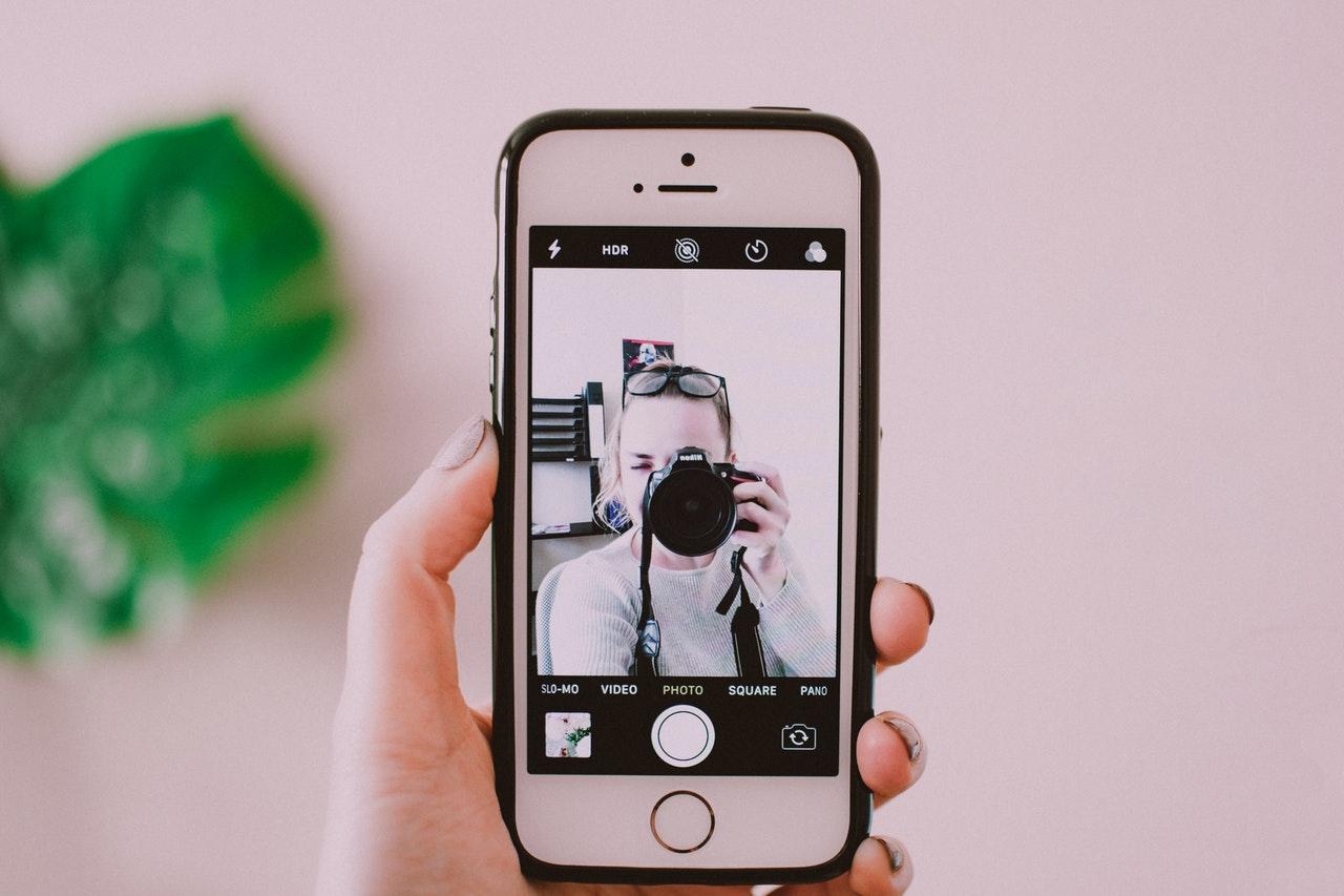 Een persoon die een selfie maakt met een iPhone