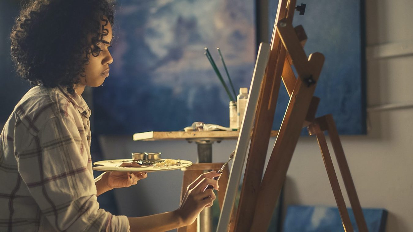 Side view of woman painting on an easel