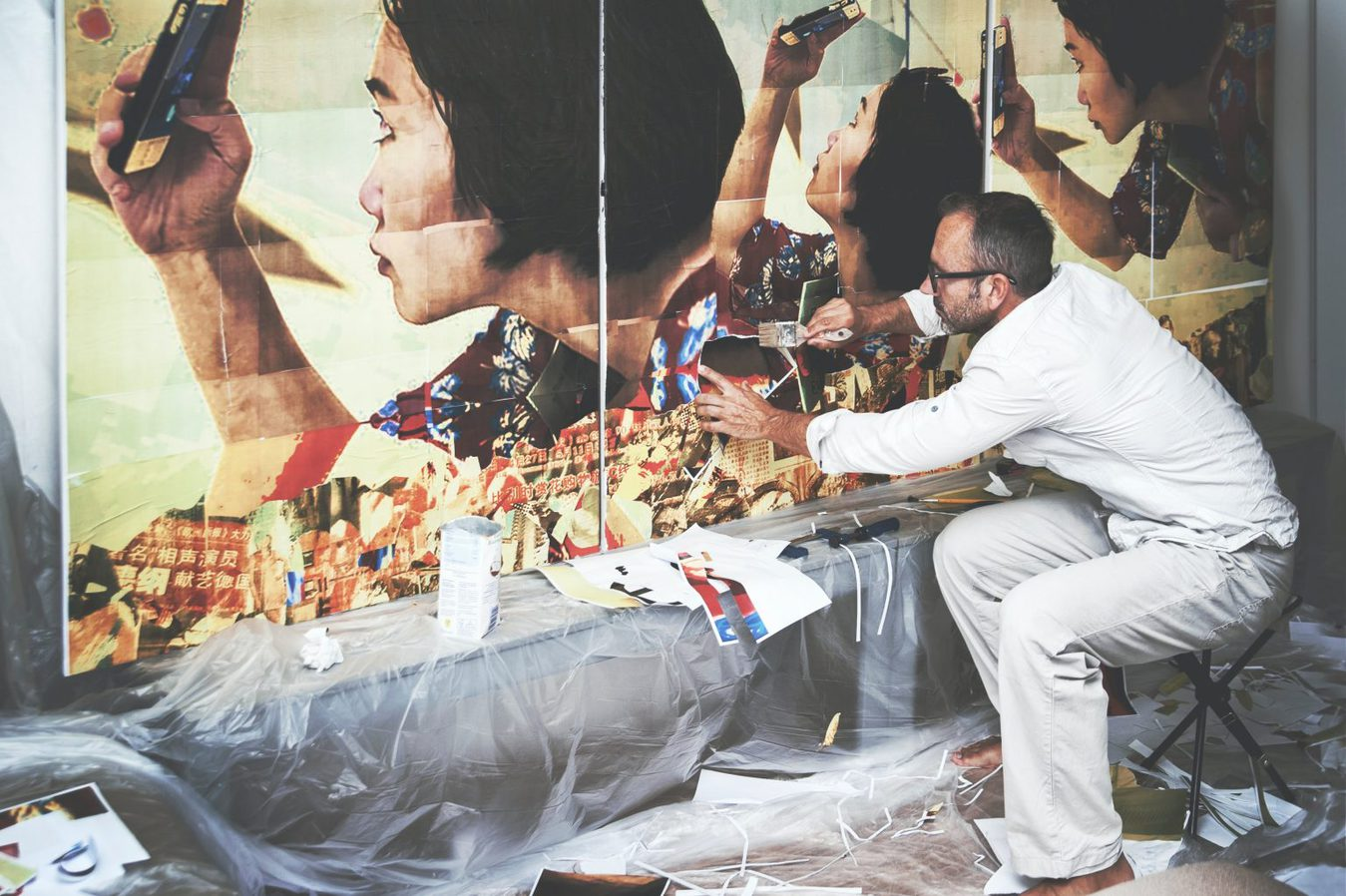 man creating wall collage