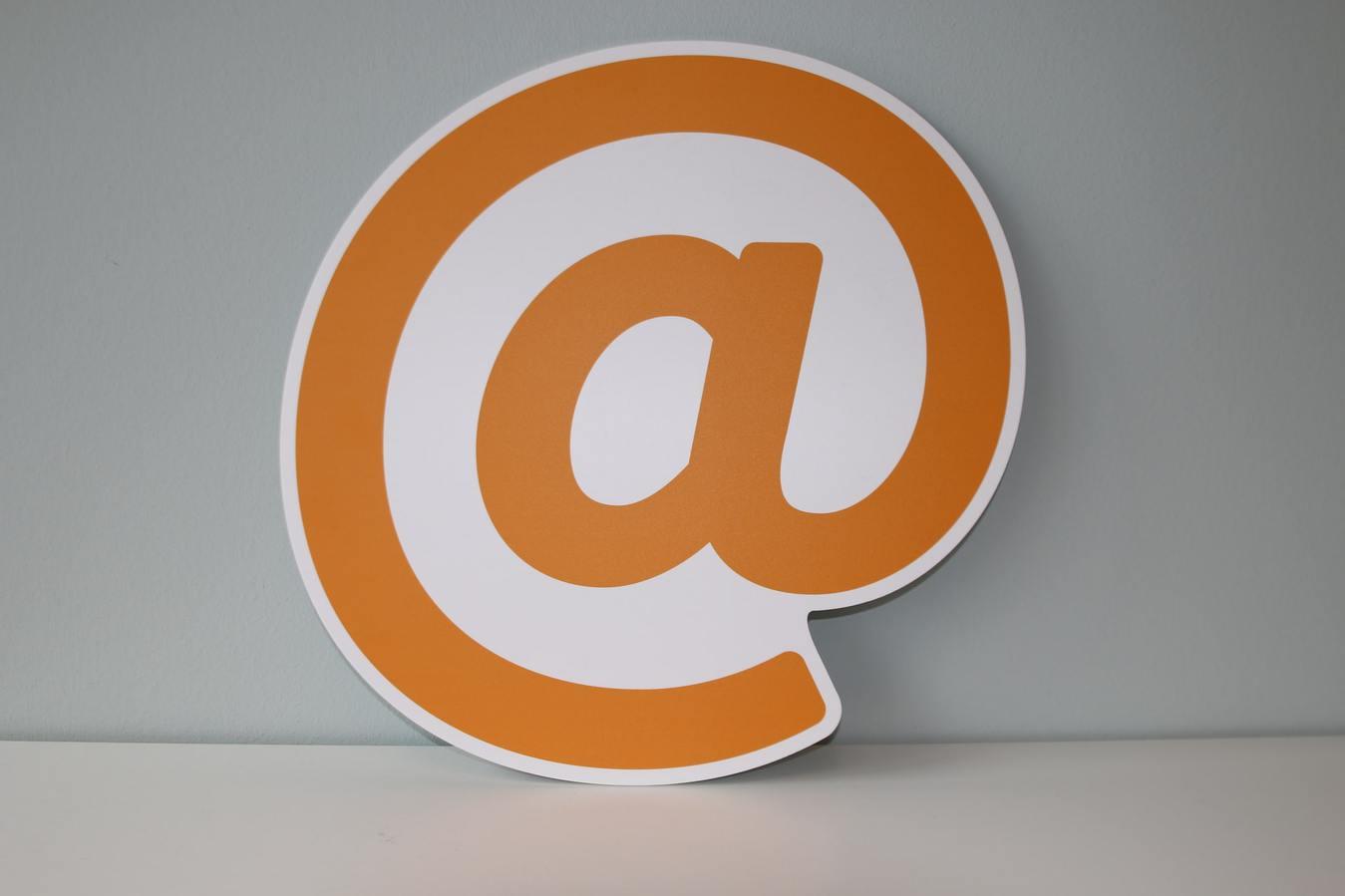 Símbolo de arroba laranja com fundo cinza