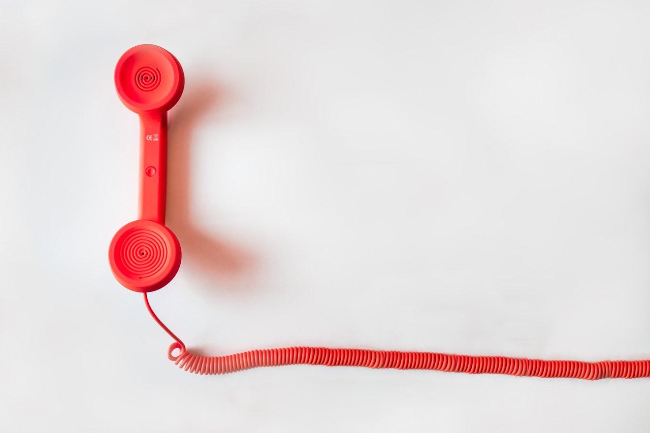 Telefono rosso su uno sfondo bianco