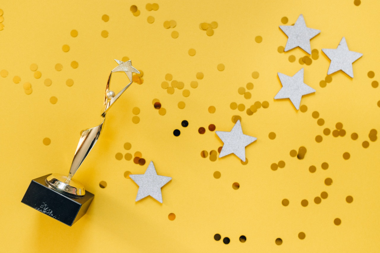 A trophy and stars against a yellow background